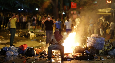 An anti-government protester sits in front of rubbish set on fire by protesters as they clash with riot police in central Ankara