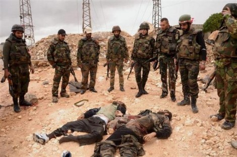 Forces loyal to Syria's President Bashar al-Assad stand near the dead bodies of two members of the Free Syrian Army at the Shikh Saad neighbourhood, in Aleppo