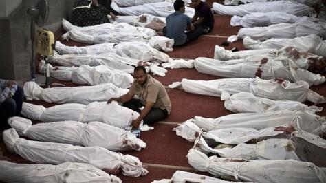 Des égyptiens en deuil près de corps enveloppés dans des linceuls dans une mosquée du Caire – le 15 Août 2013 (AFP Photo / Mahmoud Khaled)