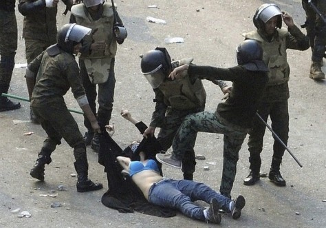 Image: Egyptian soldiers arrest a female protester during clashes in Cairo's Tahrir Square on Saturday