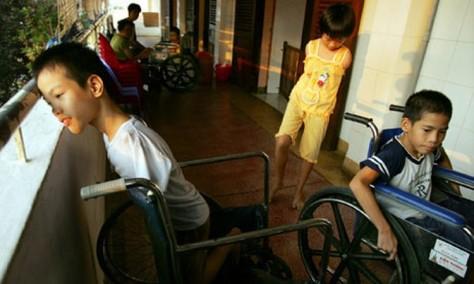 Des enfants handicapés jouant à l'extérieur d'un hôpital de Ho Chi Minh la Ville.  Beaucoup de ces malformations  seraient le résultat de la dioxine chimique que les Etats-Unis ont utilisée pendant la guerre du Viêt Nam. Photographe : Paula Bronstein/Getty Images