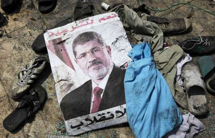 A poster of deposed Egyptian President Mursi lies amid the debris of a cleared protest camp outside the burnt Rabaa Adawiya mosque in Cairo