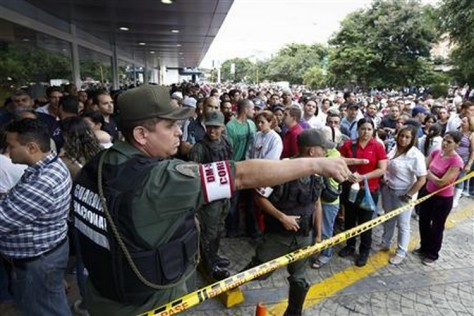 Venezuelan soldiers control the crowd as people wait to shop for electronic goods outside a Daka store in Caracas